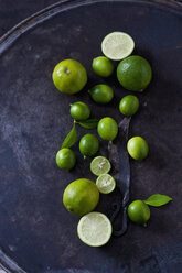 Sliced and whole limequats, limes, leaves and old knife on dark ground - CSF28694