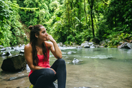 Costa Rica, Arenal Volcano National Park, Woman sitting on a stone of the river Fortuna - KIJF01856