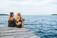 Panama, Bocas del Toro, Two women sitting on wooden jetty - KIJF01874