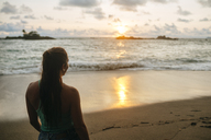Costa Rica, Woman watching the sunset at Corcovado beach - KIJF01892
