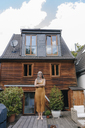 Woman standing on terrace of her house - KNSF03458
