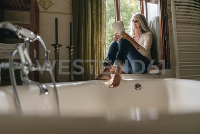 Woman sitting on window sill in the bathroom reading a book - KNSF03461 - Kniel Synnatzschke/Westend61