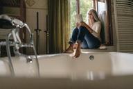 Woman sitting on window sill in the bathroom reading a book - KNSF03461