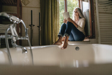 Woman sitting on window sill in the bathroom reading a book - KNSF03461