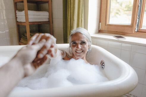 Portrait of happy woman taking bubble bath holding hands - KNSF03467