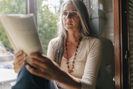 Portrait of woman sitting on window sill at home reading a book - KNSF03470