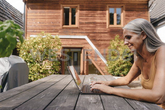 Woman sitting on terrace of her house using laptop - KNSF03476 - Kniel Synnatzschke/Westend61