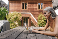 Woman sitting on terrace of her house using laptop - KNSF03476