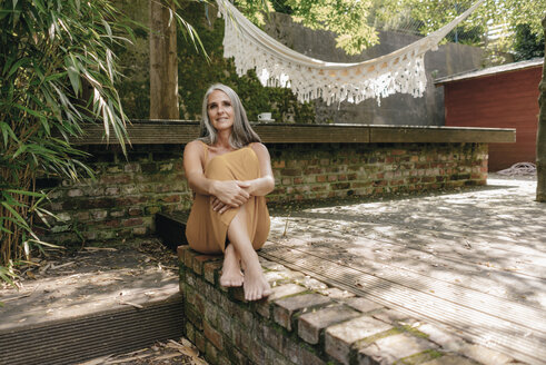 Portrait of smiling woman sitting barefoot on terrace in the backyard - KNSF03479