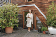 Woman standing on terrace of her house enjoying tranquility - KNSF03485