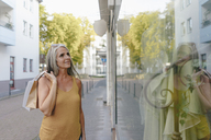 Portrait of smiling woman carrying shopping bags looking in shop window - KNSF03488