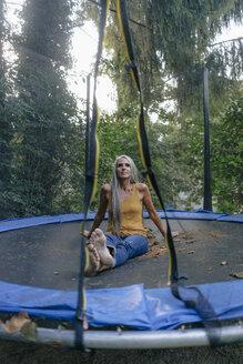 Portrait of smiling woman sitting on trampoline in the garden - KNSF03494
