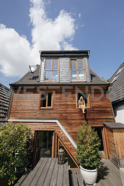 Woman sitting on window sill of her house sunbathing - KNSF03497 - Kniel Synnatzschke/Westend61