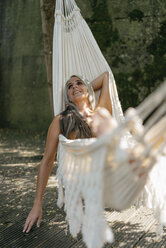 Happy woman relaxing in hammock in the garden - KNSF03506