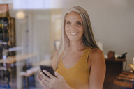 Portrait of smiling businesswoman with cell phone in her shop - KNSF03521