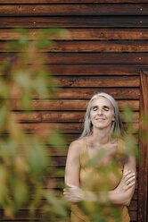Portrait of smiling mature woman standing in front of wooden facade - KNSF03524