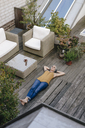 Woman relaxing on terrace listening music with headphones - KNSF03533