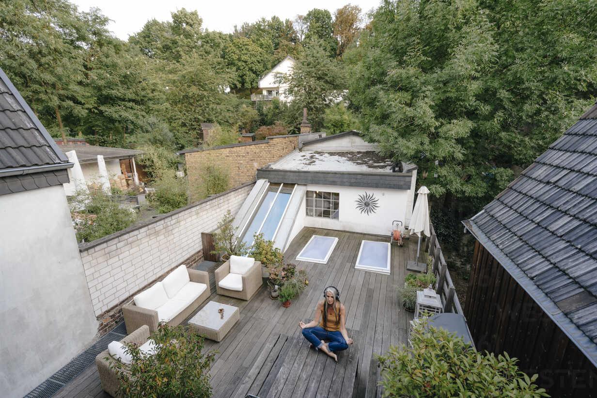 Woman with headphones sitting on terrace doing yoga exercise - KNSF03536 - Kniel Synnatzschke/Westend61