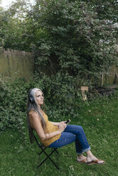 Woman with cell phone sitting in the garden listening music with headphones - KNSF03539