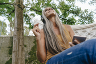 Woman with cell phone sitting in the garden listening music with headphones - KNSF03542