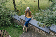 Woman sitting on wall in the garden listening music with headphones - KNSF03545