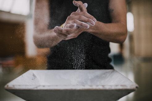 Athlete applying chalk on his hands - OCAF00007