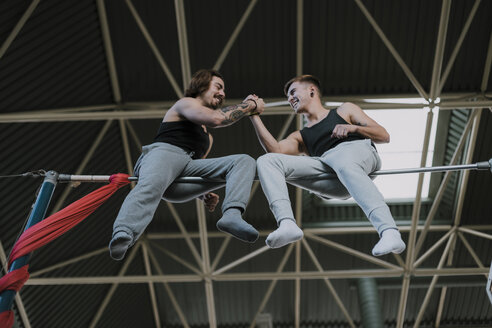 Two smiling gymnasts sitting on high bar shaking hands in gym - OCAF00013