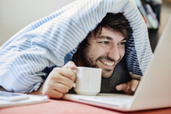 Portrait of laughing young man lying on bed with cup of coffee using laptop - JATF00976