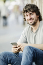 Portrait of smiling young man with cell phone outdoors - JATF00979