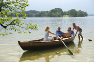 Germany, Bavaria, Murnau, family in rowing boat at lakeshore - ECPF00147