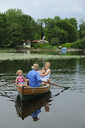 Happy family in rowing boat on lake - ECPF00162