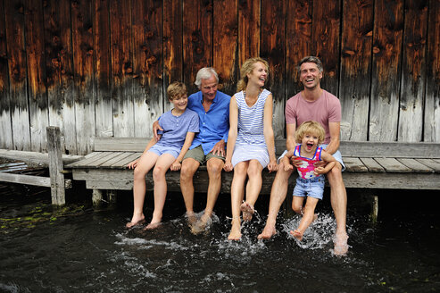 Family sitting together on jetty splashing with water - ECPF00165