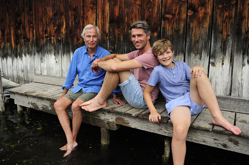 Boy sitting with grandfather and father together on jetty in summer - ECPF00168