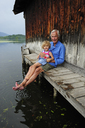 Little girl sitting with grandfather on jetty in summer - ECPF00171