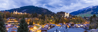 Switzerland, Canton of Bern, Gstaad, townscape with Gstaad Palace Hotel at dusk - WDF04299