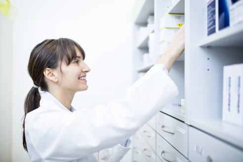 Smiling pharmacist checking medicine at cabinet in pharmacy - WESTF23912