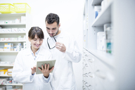 Two pharmacists using tablet in pharmacy - WESTF23918