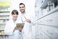 Portrait of two smiling pharmacists with tablet in pharmacy - WESTF23921