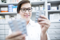 Smiling pharmacist holding tablet package in pharmacy - WESTF23927