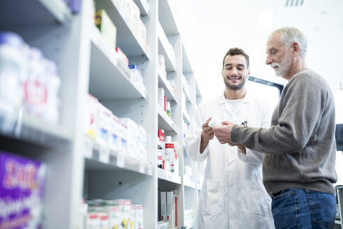 Pharmacist advising customer in pharmacy - WESTF23936