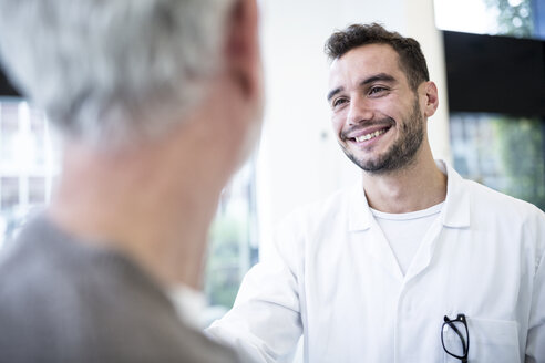 Man in doctor's overall smiling at grey-haired man - WESTF23942