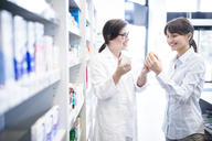 Pharmacist advising customer in pharmacy - WESTF23945
