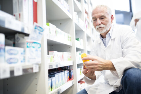 Pharmacist examining pill box in pharmacy - WESTF23954