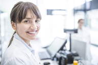 Portrait of smiling woman in lab coat - WESTF23969