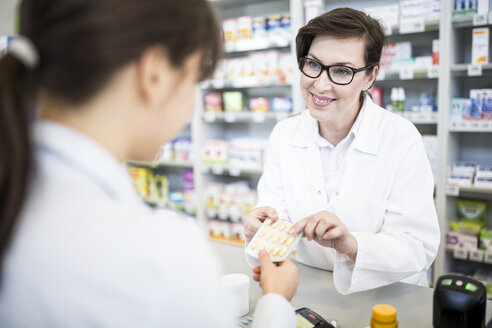 Pharmacist handing over medicine to customer in pharmacy - WESTF23972