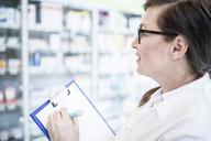 Pharmacist holding clipboard at shelf in pharmacy - WESTF23978