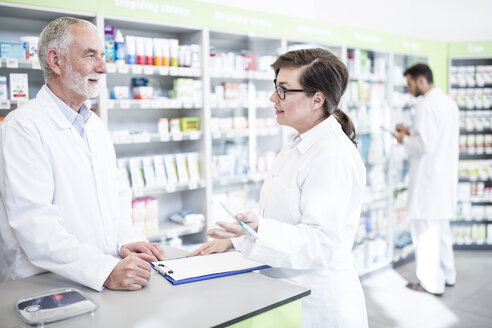 Two pharmacists with clipboard at counter in pharmacy - WESTF23981