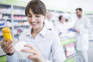 Smiling woman in pharmacy holding medicine - WESTF23984