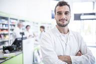 Portrait of smiling pharmacist in pharmacy with colleagues in background - WESTF23987