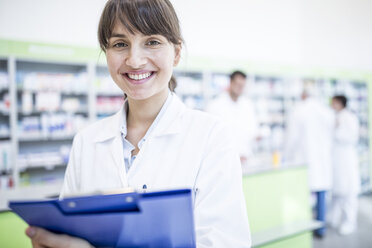 Portrait of smiling pharmacist in pharmacy holding clipboard - WESTF23990
